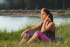 A mulher atrativa desportiva nos lagos costeia a música de escuta Fotos de Stock Royalty Free
