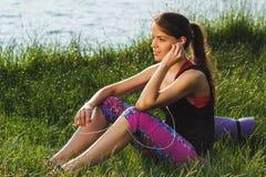 A mulher atrativa desportiva nos lagos costeia a música de escuta Imagens de Stock