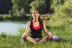 A mulher atrativa desportiva nos lagos costeia na pose dos lótus Imagem de Stock