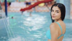 Mulher atrativa do ajuste que senta-se perto da piscina Menina bronzeada sedutor na borda da associação filme