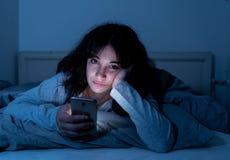 Mulher atrativa do latino dedicada ao telefone celular e ao Internet tarde em nigh na cama que olha sem sono fotografia de stock