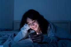 Mulher atrativa do latino dedicada ao telefone celular e ao Internet tarde em nigh na cama que olha sem sono fotos de stock