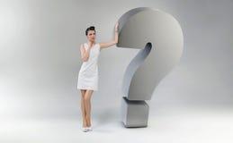 Mulher atrativa e surpreendida que inclina-se contra a pergunta março Fotografia de Stock Royalty Free