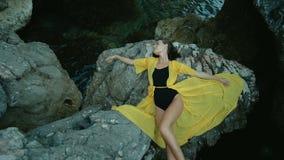 A mulher atrativa encontra-se na rocha pela costa de mar no dia de verão video estoque