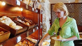 A mulher atrativa escolhe o pão no café com autosserviço filme