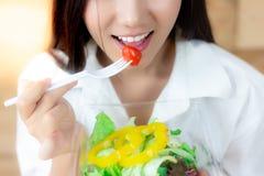 A mulher atrativa está comendo vegetais ou tomate usando a forquilha C imagem de stock royalty free