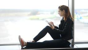 A mulher atrativa está sentando-se perto da janela e está verificando-se a informação do portátil em linha no aeroporto vídeos de arquivo