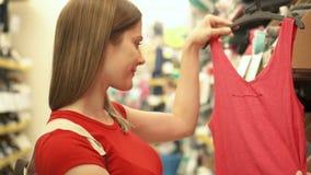 Mulher atrativa feliz na compra vermelha do t-shirt na roupa de compra da alameda Conceito do shopaholism da consumição video estoque