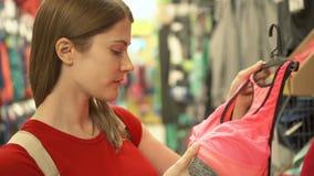 Mulher atrativa feliz na compra vermelha do t-shirt na roupa de compra da alameda Conceito do shopaholism da consumição vídeos de arquivo