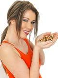 Mulher atrativa feliz nova que guarda um punhado de porcas misturadas imagem de stock royalty free