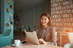 Mulher atrativa feliz que olha vídeos engraçados ao consultar páginas de Internet em sua tabuleta digital imagens de stock royalty free