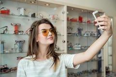 A mulher atrativa foi na compra apenas, fazendo o selfie ao tentar em óculos de sol à moda novos na loja do ótico, enviando imagem de stock