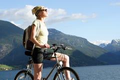 Mulher atrativa na bicicleta nas montanhas Fotos de Stock Royalty Free