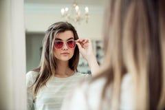Mulher atrativa na caça para coisas na moda novas Retrato interno da mulher caucasiano nova à moda na loja do ótico imagem de stock