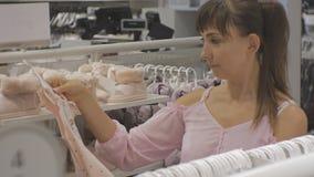 Mulher atrativa na loja da roupa do bebê Close-up do vestido de escolha fêmea caucasiano do bebê video estoque
