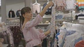 Mulher atrativa na loja da roupa do bebê Tiro médio do vestido de escolha fêmea caucasiano do bebê filme