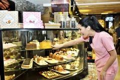 Mulher atrativa no café que escolhe o bolo imagem de stock