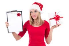 Mulher atrativa no chapéu de Santa com levantamento da lista de objetivos pretendidos isolado sobre Imagem de Stock Royalty Free
