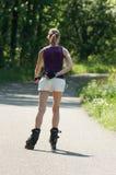A mulher atrativa no rolo de movimentações do short patina na floresta da beira Foto de Stock