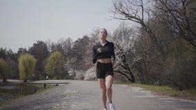 Mulher atrativa no sportswear que corre no riverbank Estilo de vida ativo, esporte A senhora que mantém seu corpo na forma filme