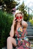 Mulher atrativa nova Óculos de sol vermelhos, vestido da cor, telefone celular, 5G, 4G, 3G, 2G, rede de LTE imagem de stock