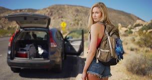 A mulher atrativa nova abandona o veículo no deserto para roubar a Fotografia de Stock Royalty Free