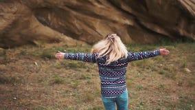 A mulher atrativa nova agradável com cabelo louro do voo gerencie ao redor no fundo de um campo verde e de uns penhascos íngremes filme