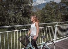 Mulher atrativa nova com bicicleta em uma ponte foto de stock