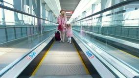 Mulher atrativa nova com mala de viagem e sua filha bonita que vai abaixo da escada rolante no aeroporto filme