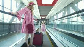 A mulher atrativa nova com a mala de viagem que vai abaixo da escada rolante e de sua filha bonita corre após sua mãe no filme