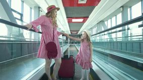 A mulher atrativa nova com a mala de viagem que vai abaixo da escada rolante e de sua filha bonita corre após sua mãe no video estoque