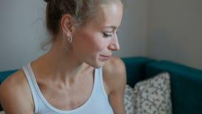 A mulher atrativa nova com o copo branco nas mãos senta-se em casa no sofá filme
