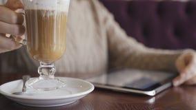 Mulher atrativa nova com o tablet pc que senta-se no café filme