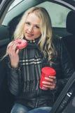 Mulher atrativa nova com um copo da bebida e da filhós quentes Imagens de Stock