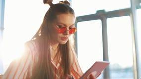 Mulher atrativa nova em óculos de sol vermelhos usando o tablet pc com écran sensível em um café Menina bonita no aeroporto ou video estoque