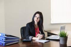 Mulher atrativa nova em um terno de negócio que toma notas no bloco de notas na mesa no escritório Fotografia de Stock