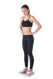 A mulher atrativa nova está em escalas do peso Foto de Stock Royalty Free