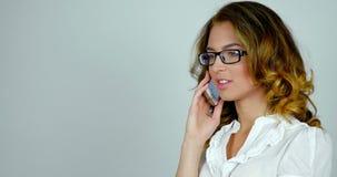 A mulher atrativa nova fala no telefone e move seu olhar, reflexões em seus vidros filme