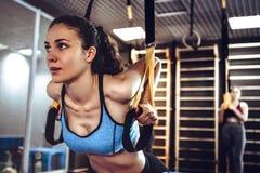 A mulher atrativa nova faz o treinamento oblíquo do Abs do núcleo com as correias da aptidão no estúdio do gym imagens de stock