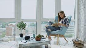 A mulher atrativa nova leu o livro e bebeu o café que senta-se no balcão no apartamento moderno do sótão filme