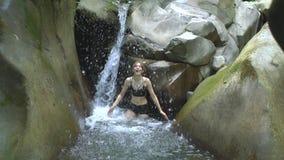 Mulher atrativa nova no movimento lento que espirra a água clara do lago da montanha com a cachoeira pequena em tropical verde filme