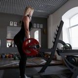 A mulher atrativa nova no sportswear preto nas sapatilhas aumenta o barbell no treinamento no gym Menina que faz exercícios da fo imagem de stock