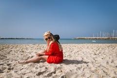 A mulher atrativa nova no vestido vermelho brilhante senta-se sobre na praia imagens de stock royalty free