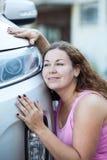 Mulher atrativa nova que adora seu carro novo Fotografia de Stock