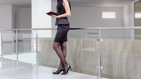 Mulher atrativa nova que anda em um escritório, lendo a informação no caderno vídeos de arquivo