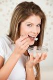 Mulher atrativa nova que come o yogurt foto de stock