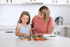 Mulher atrativa nova que cozinha junto com seus 6 ou 7 anos pequenos louros bonitos doces do sa de preparação feliz de sorriso da Fotos de Stock