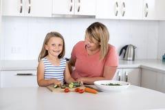 Mulher atrativa nova que cozinha junto com seus 6 ou 7 anos pequenos louros bonitos doces do sa de preparação feliz de sorriso da Foto de Stock Royalty Free