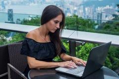 Mulher atrativa nova que datilografa ou que trabalha no portátil que senta-se no café do telhado com opinião da cidade Imagens de Stock Royalty Free