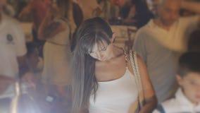 Mulher atrativa nova que escolhe lembranças no contador no quadrado aglomerado da cidade do turista na noite vídeos de arquivo